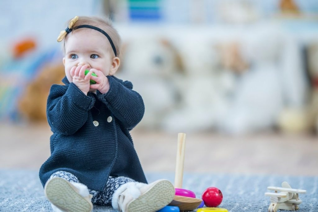 A baby chewing on a toy, showing how babies will put anything into their mouths during the teething phase.